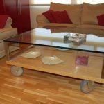 Mesa de centro con estructura de acero inoxidable, sobre de cristal, madera y ruedas